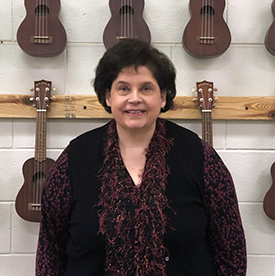 Teacher standing in front of violins on wall.