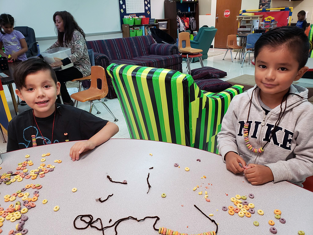Two boys sitting at a table smiling for the camera.