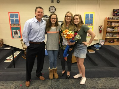 Teacher poses with her family of two daughters and her husband.