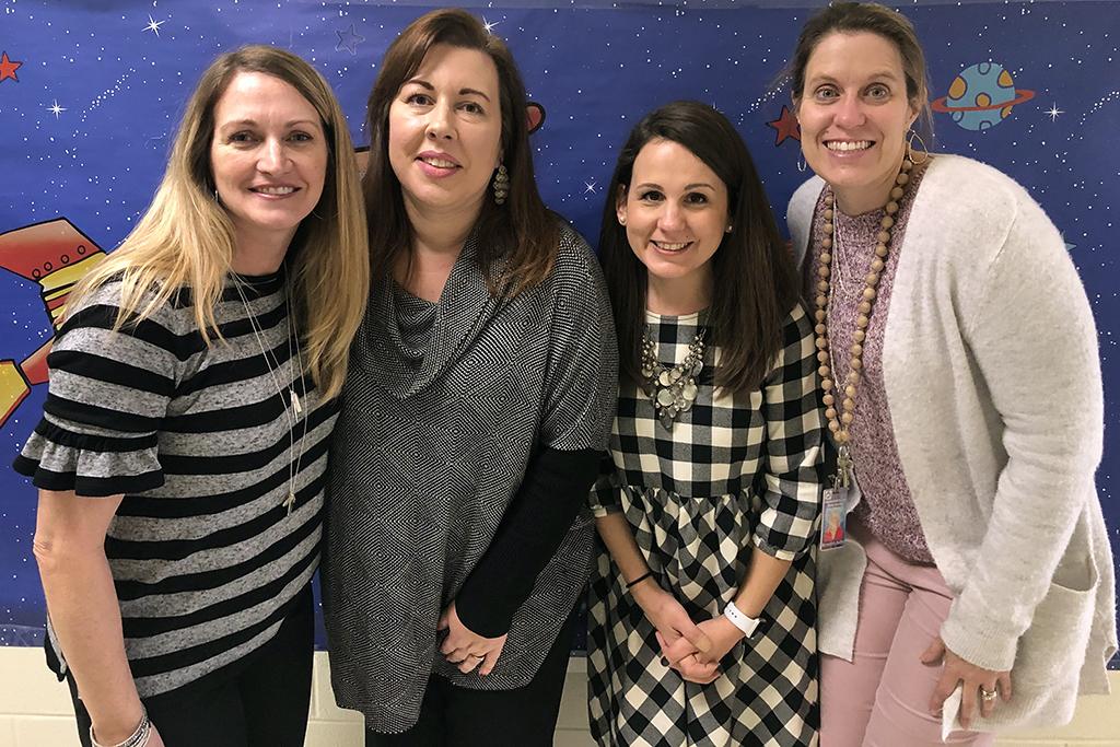 Four female teachers huddle together for a photo