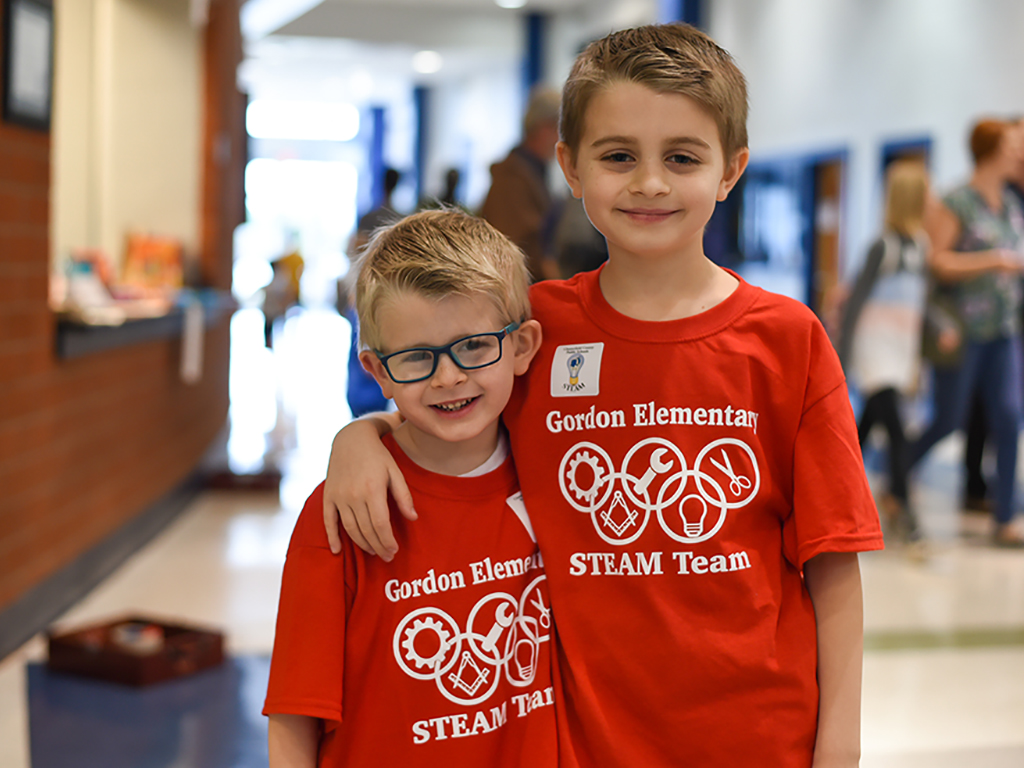 Two boys in matching steam logo t-shirts pose for a photo.