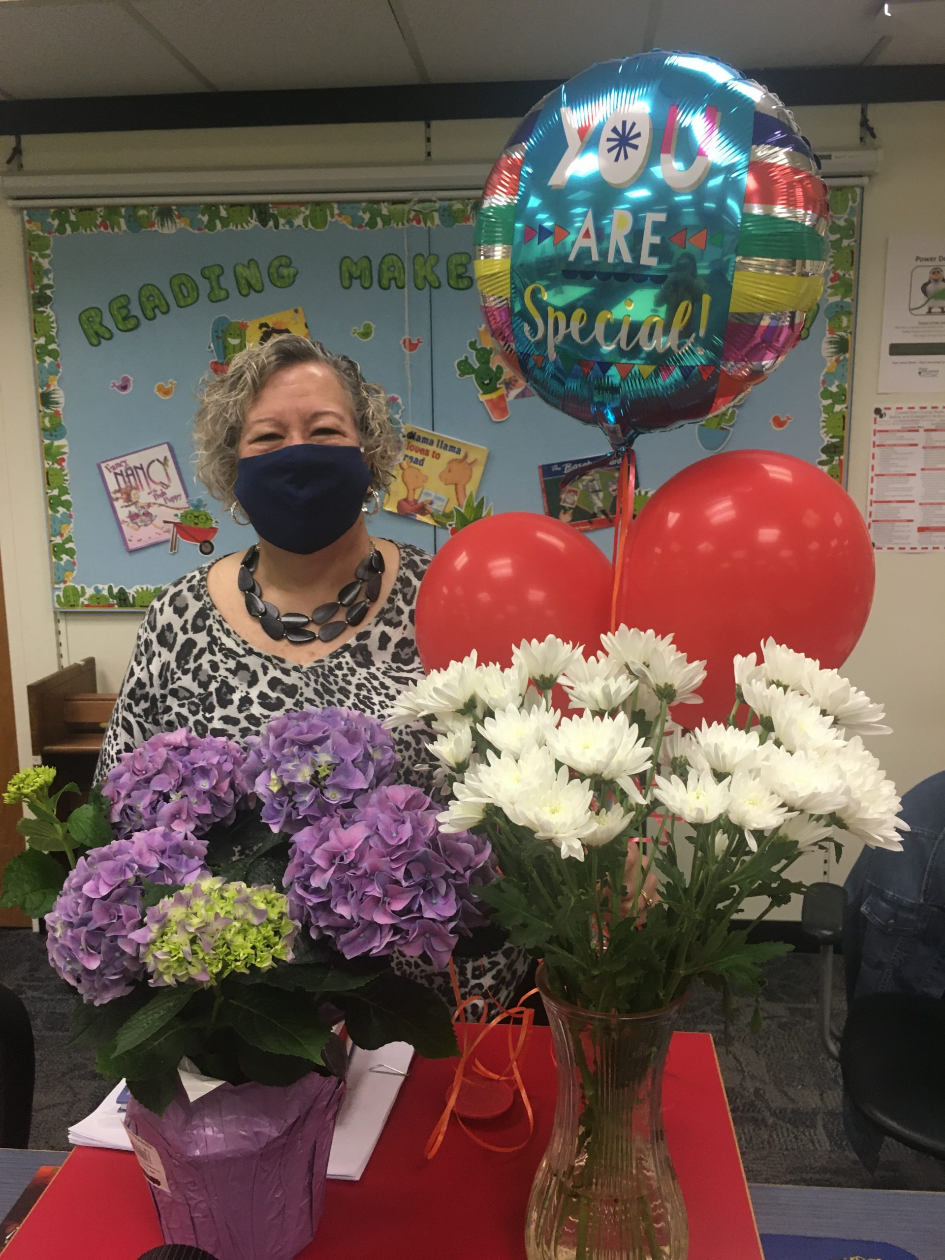 Photo of Ms. Gaines holding flowers and balloons that were presented to her.