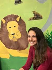 Assistant Principal posing in front of mural of a lion