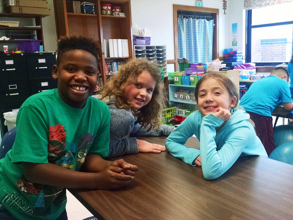 three students leaning on a table smiling for the camera