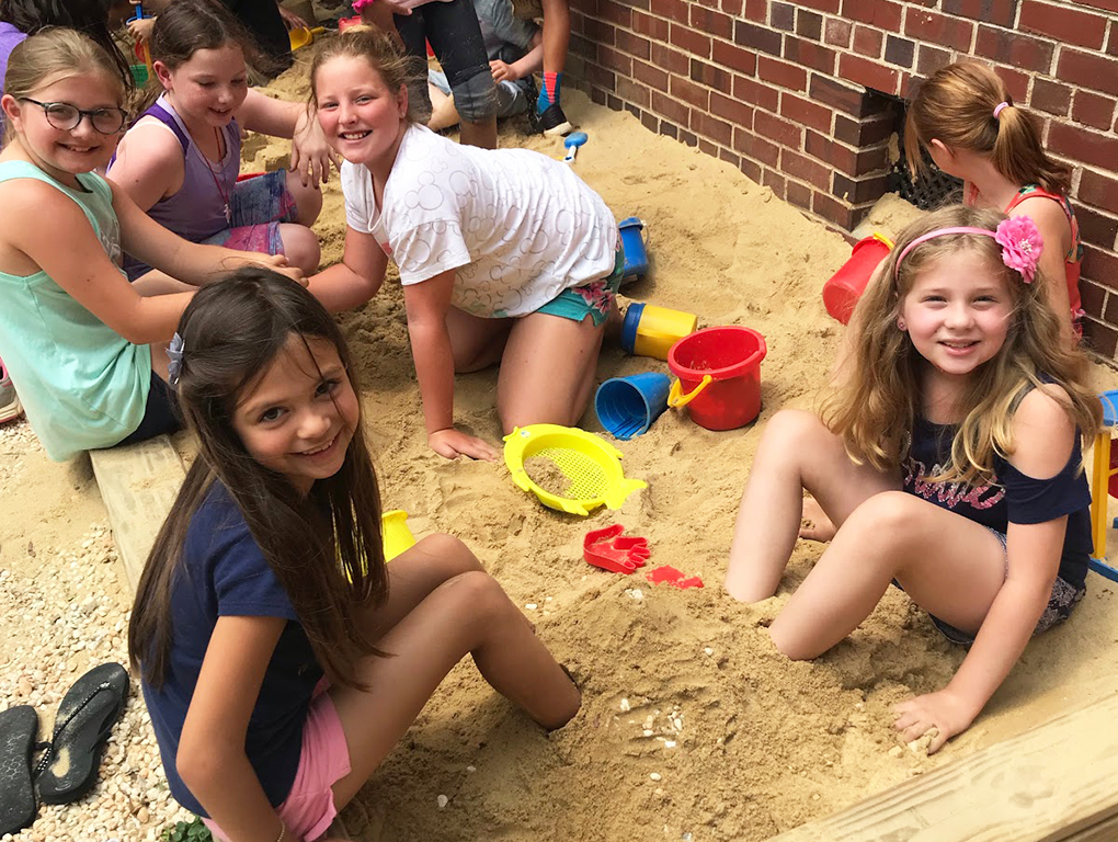 six students playing in a sandbox