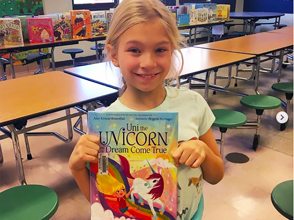 female student holding up a book about a unicorn.