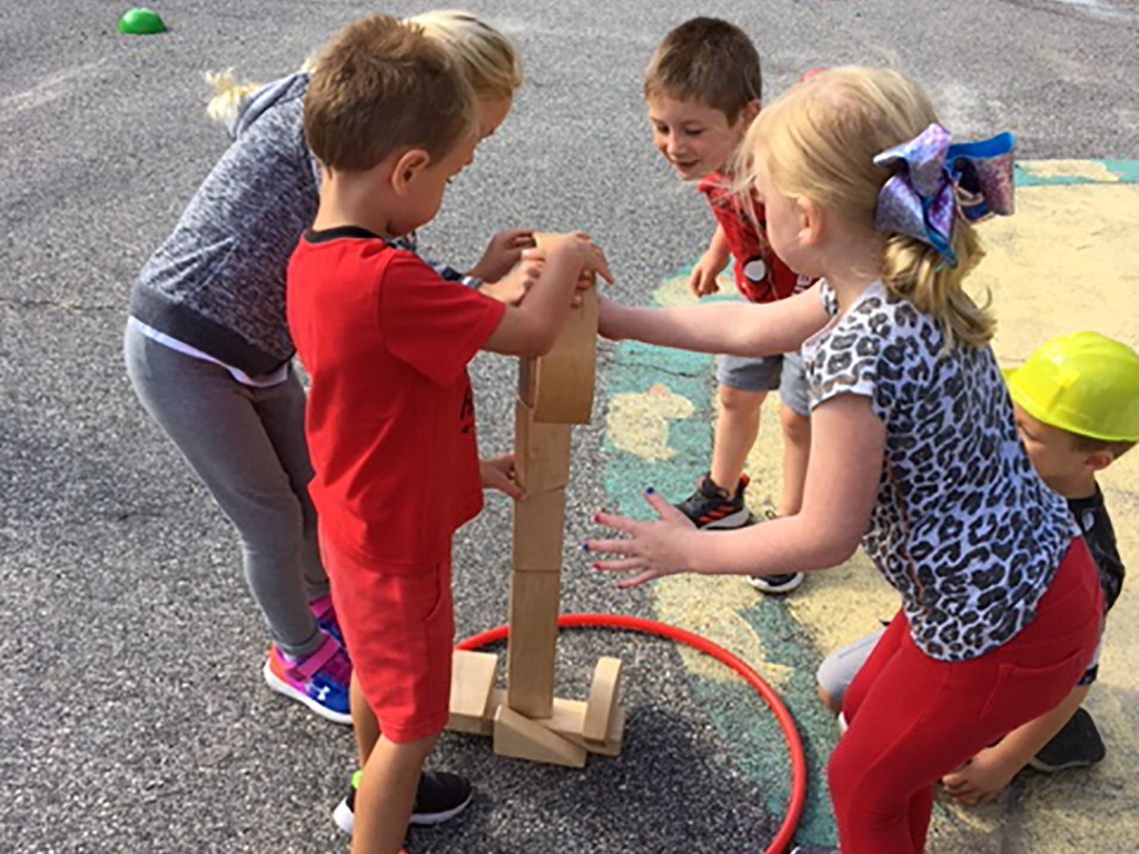 four students playing a game out on the playground