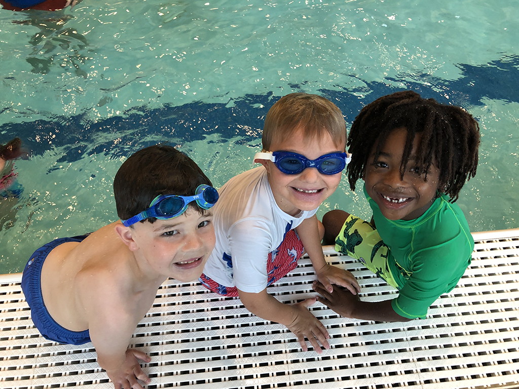 four boys sitting on the side of the pool smiling up at the camera.