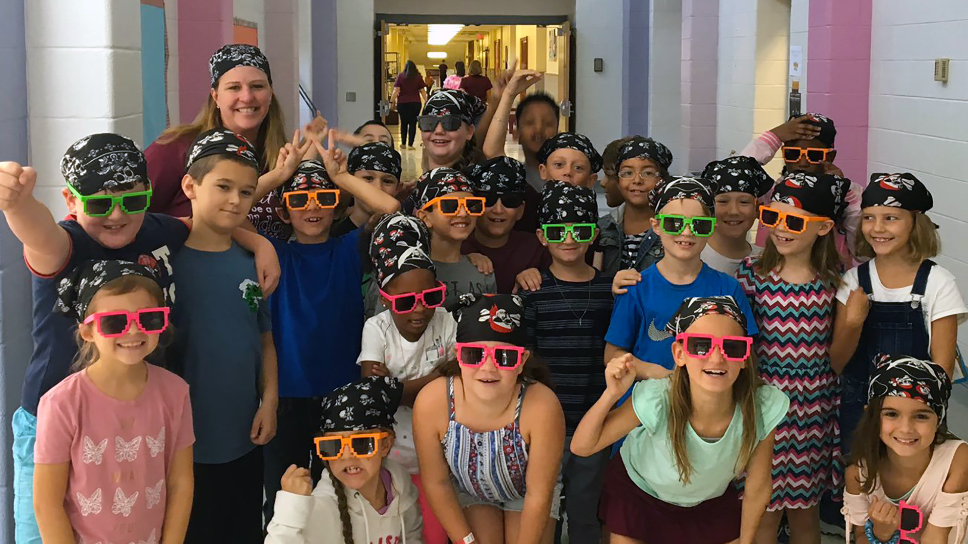 Large group of students in school hallway with colorful sunglasses on and posing for a group photo.