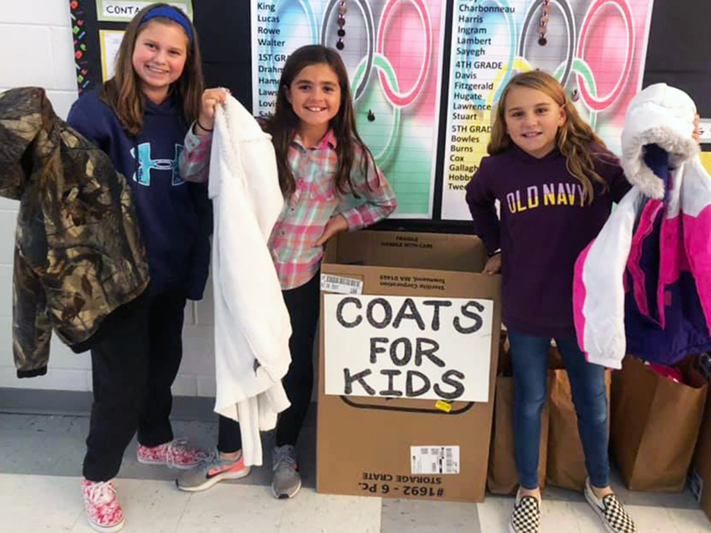 three girls holding up donated coats.