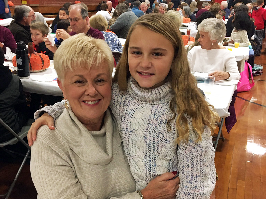 Student poses with her Grandmother in the cafeteria at the Grandparent's breakfast.