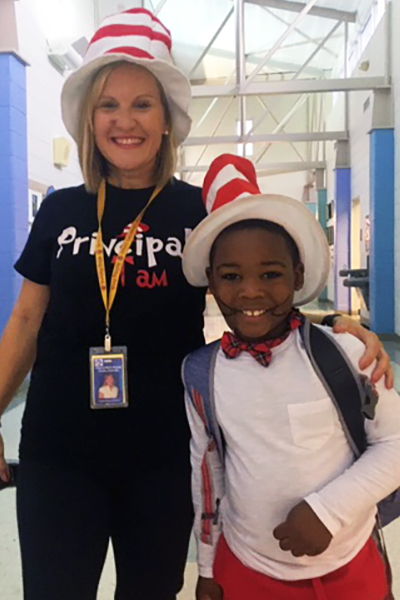 Principal Jones posing with male student both wearing Cat in the Hat outfits.