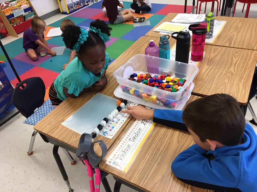 two students counting with dice at their table