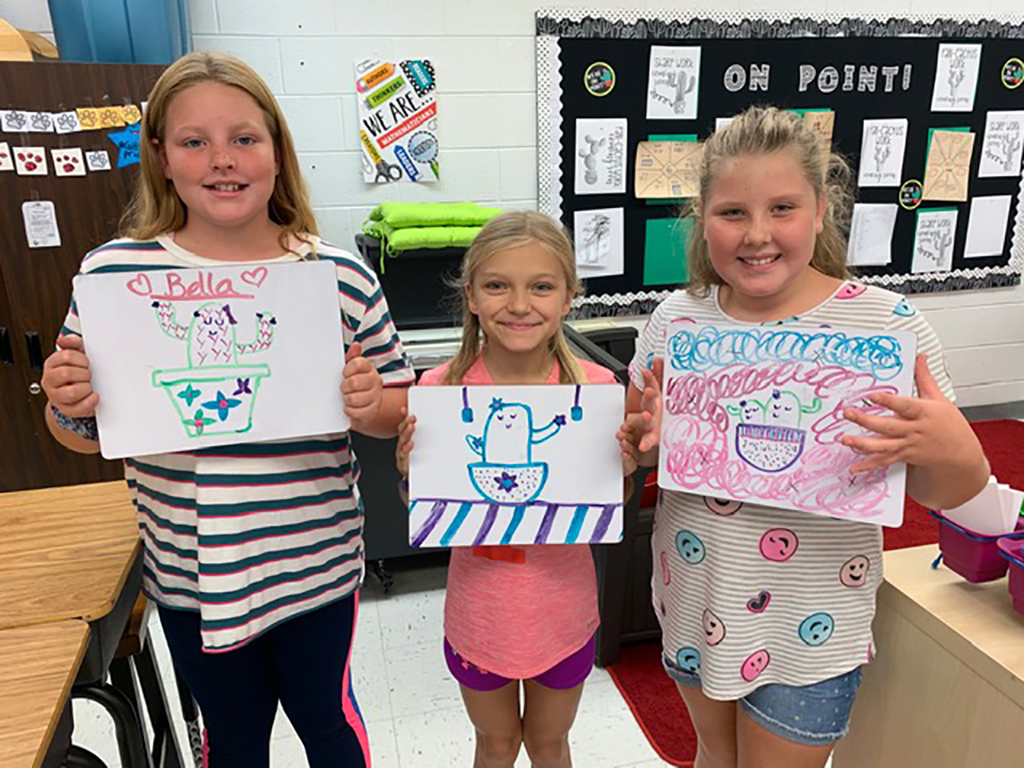 Three girls holding up their artwork.