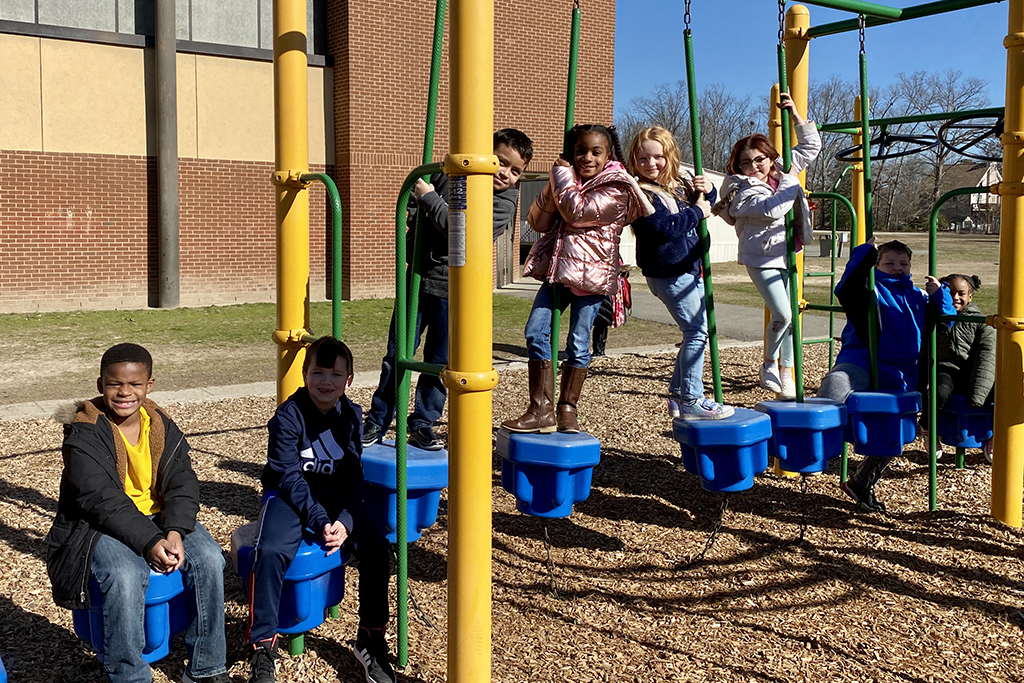 Group of students swinging and hanging onto outdoor playground equipment.