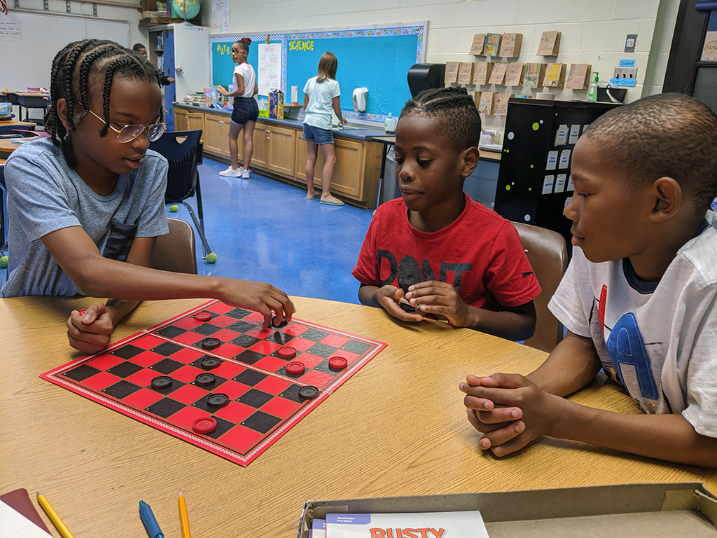 Three male students sitting at a table playing checkers.