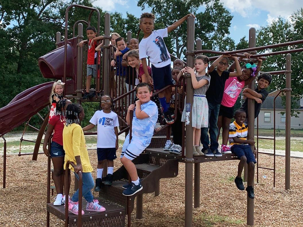 Students all posing for a photo on the playground equipment.