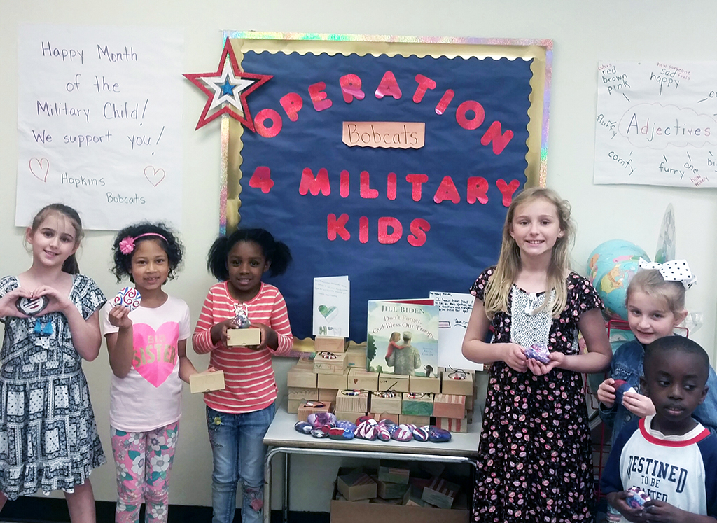 six students standing in front of a sign about military families