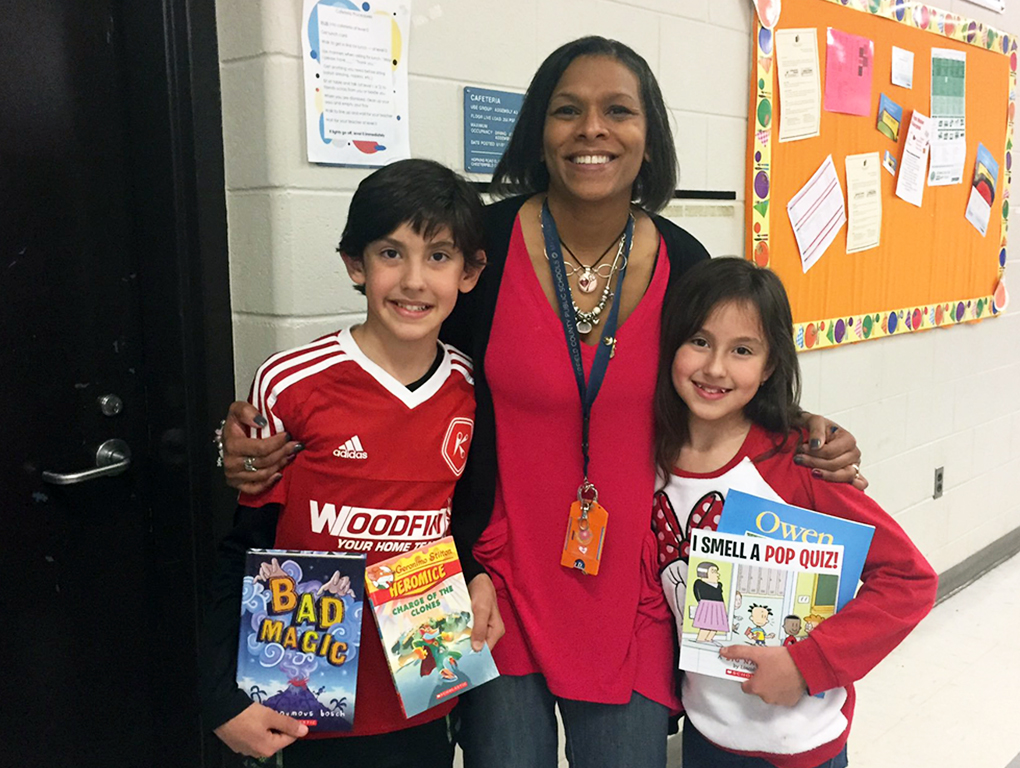 principal hugs two students holding up their library books