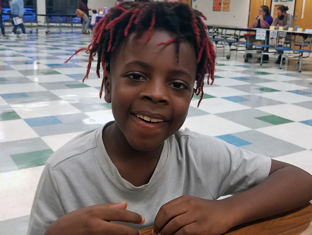 male student smiling for camera sitting in cafeteria