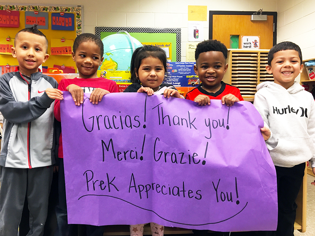 Five pre-k student hold up a thank you banner.