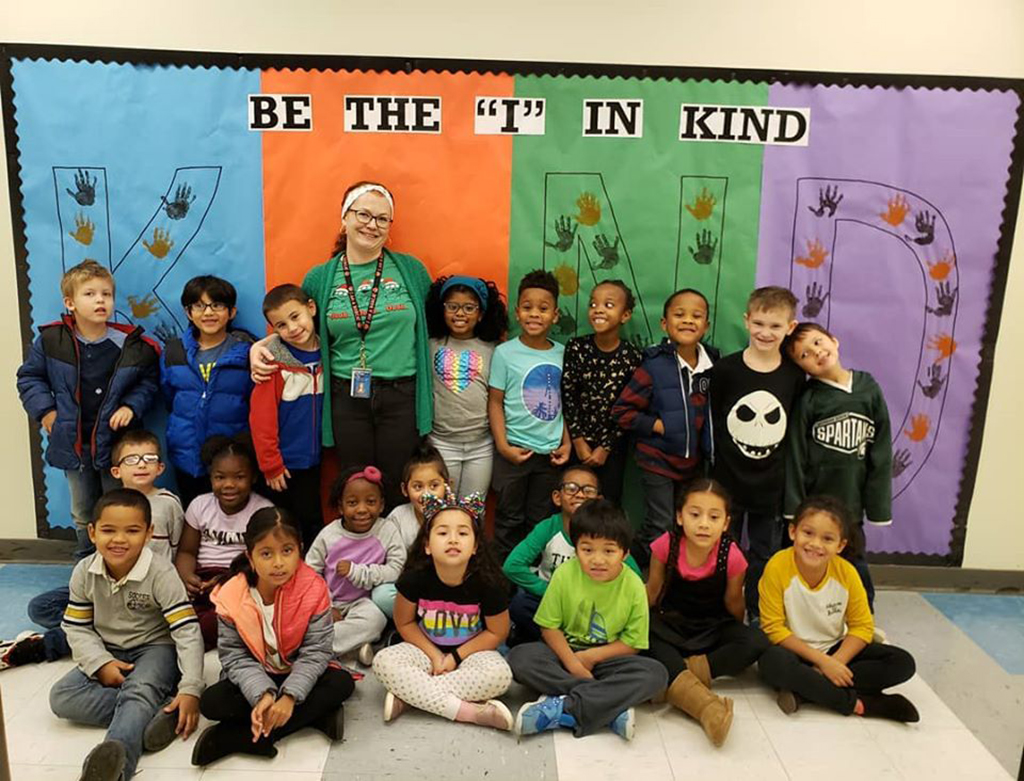 class poses in front of be kind sign.
