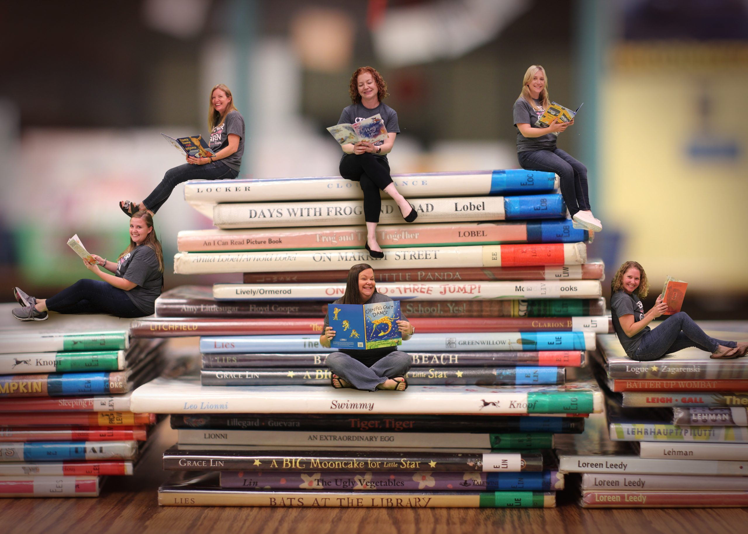 Teachers sitting on faux books.