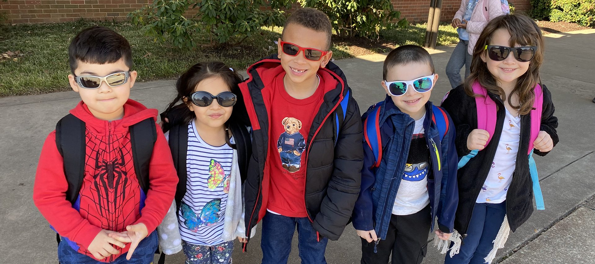Five students wearing their sunglasses.