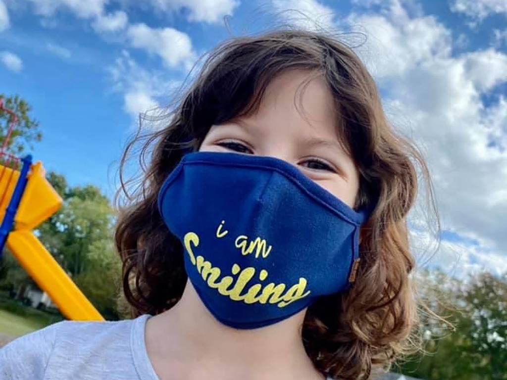 Student on playground showing off her mask. Mask says I'm Smiling.