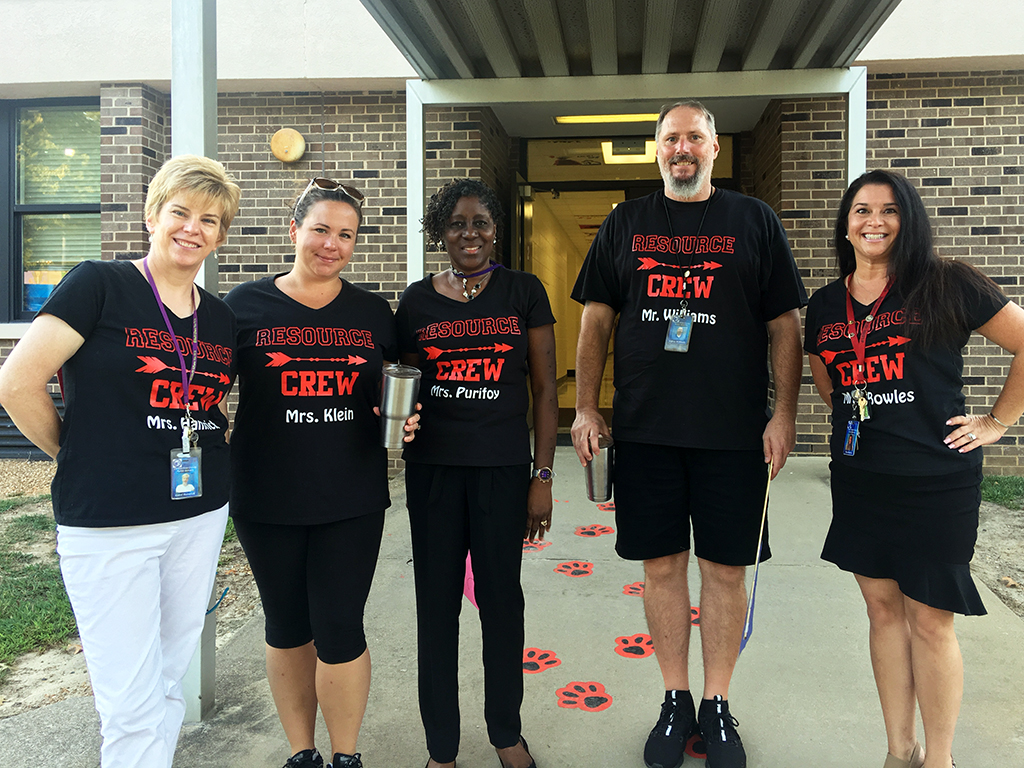 Five teachers in matching t-shirts pose for a photo.