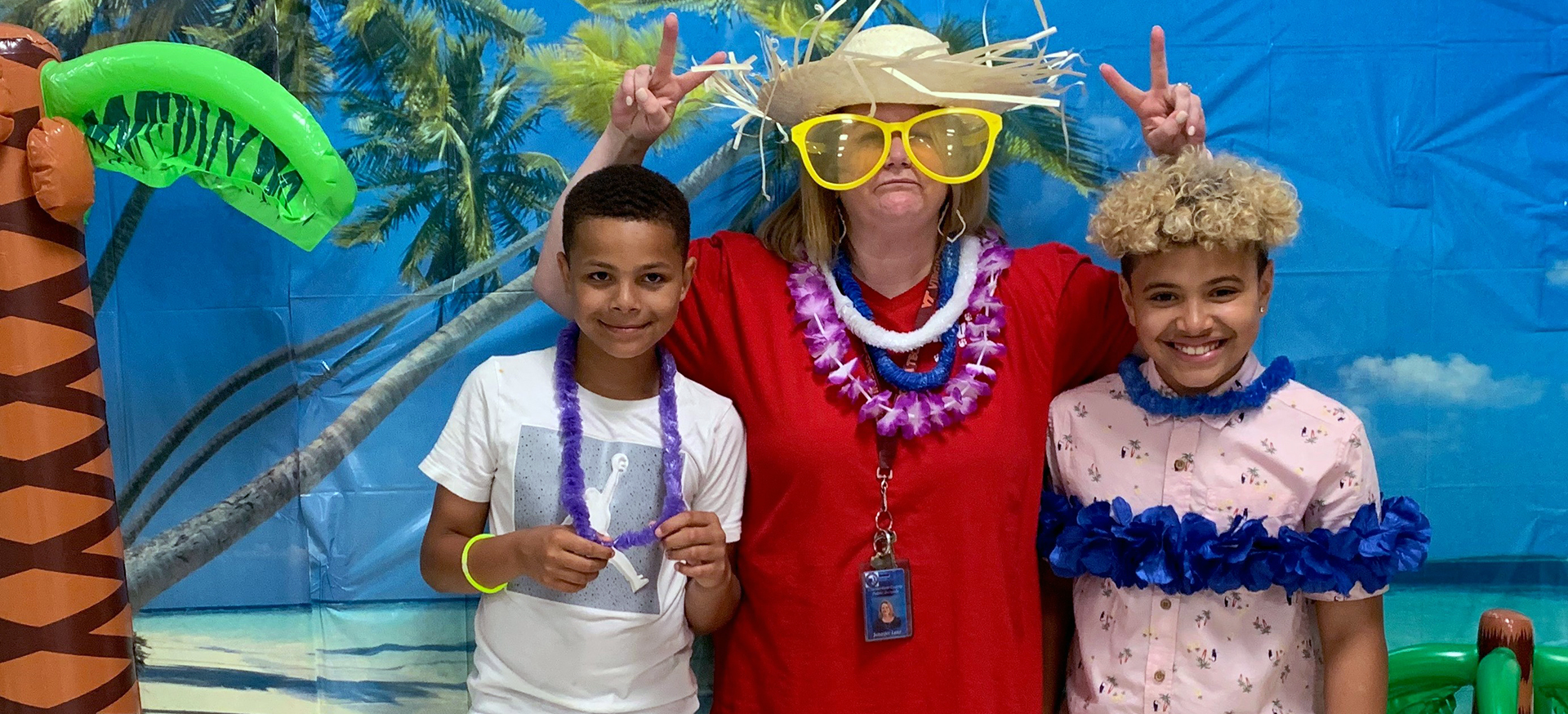 Principal posing with two students in front of faux beach backdrop.