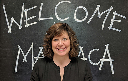 Principal posing in front of a chalkboard that says 'Welcome Matoaca'