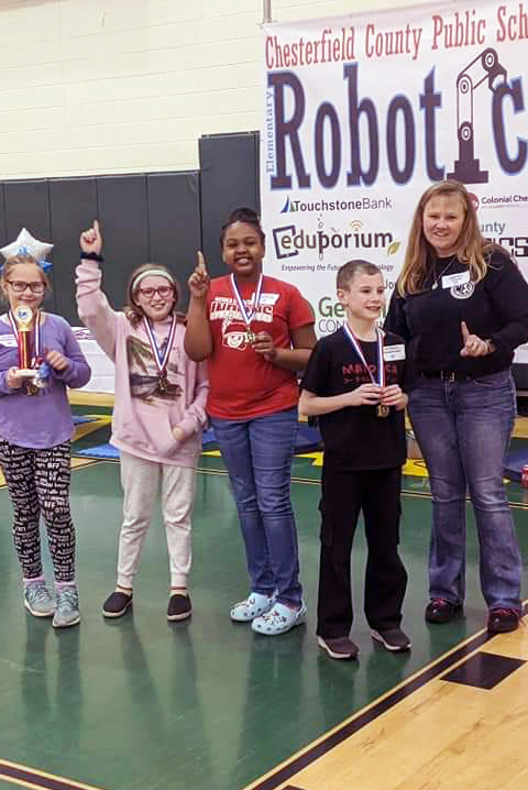Four students pose with teacher in front of Robotics Sign at competition.
