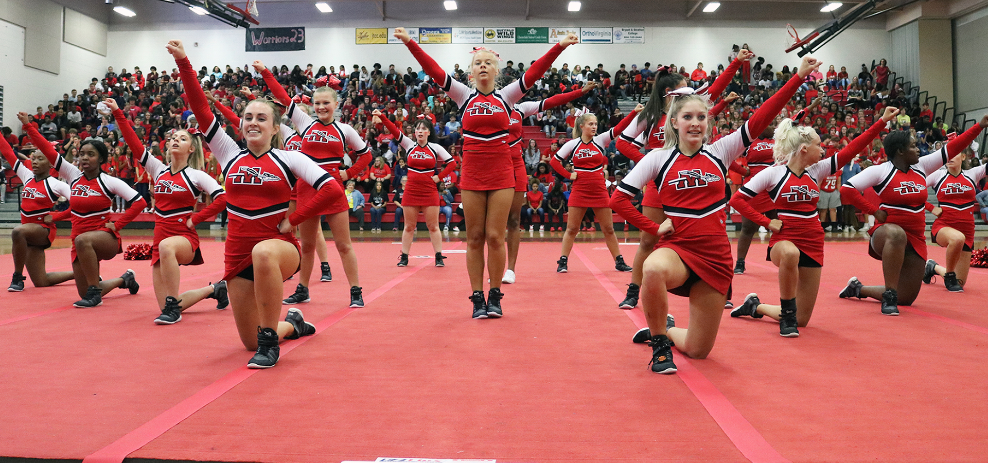 Cheerleaders all in red performing in gym with crowd in background.