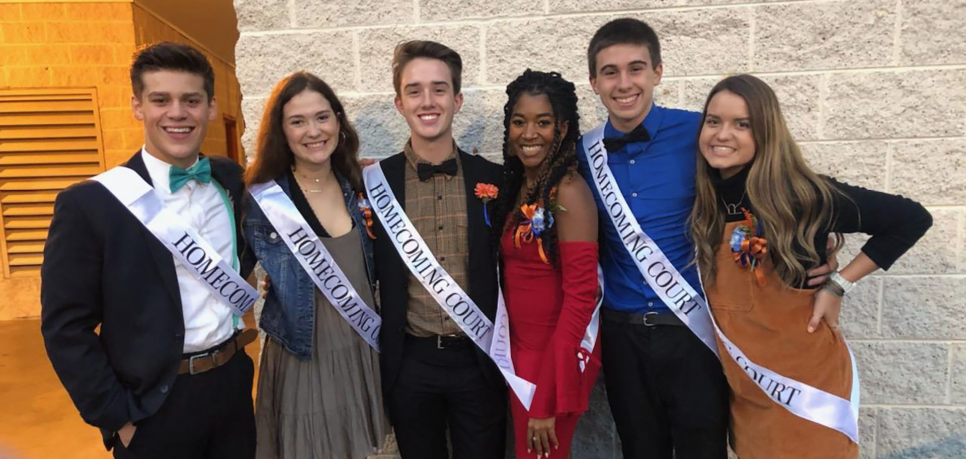 Six students pose with their homecoming court sashes on.