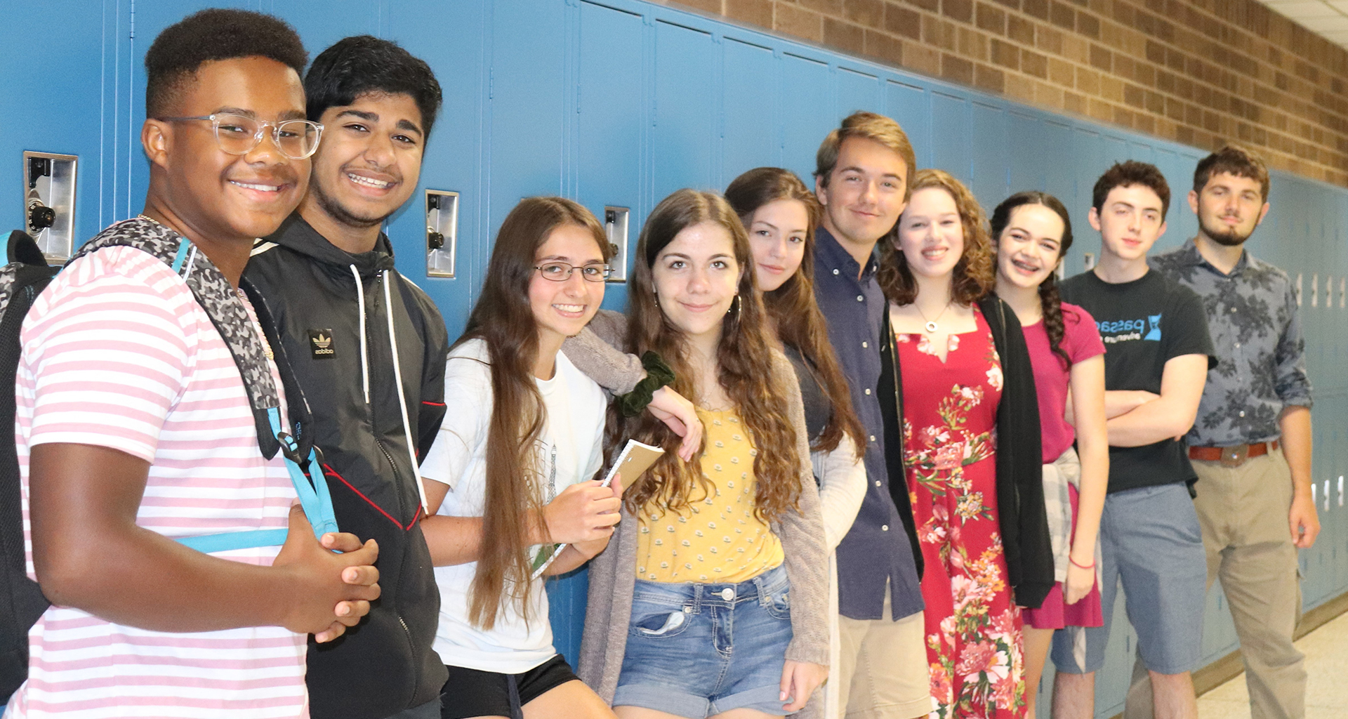 Line up of students standing against the lockers posing for a photo.