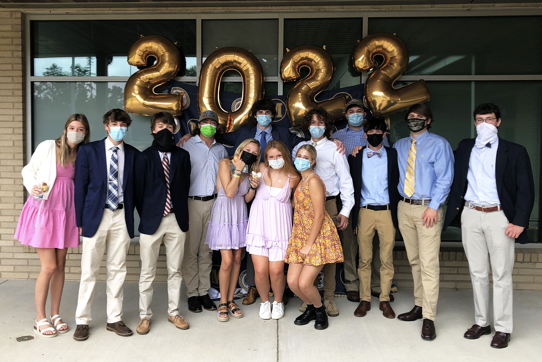 Group of students pose under a 2022 balloon.