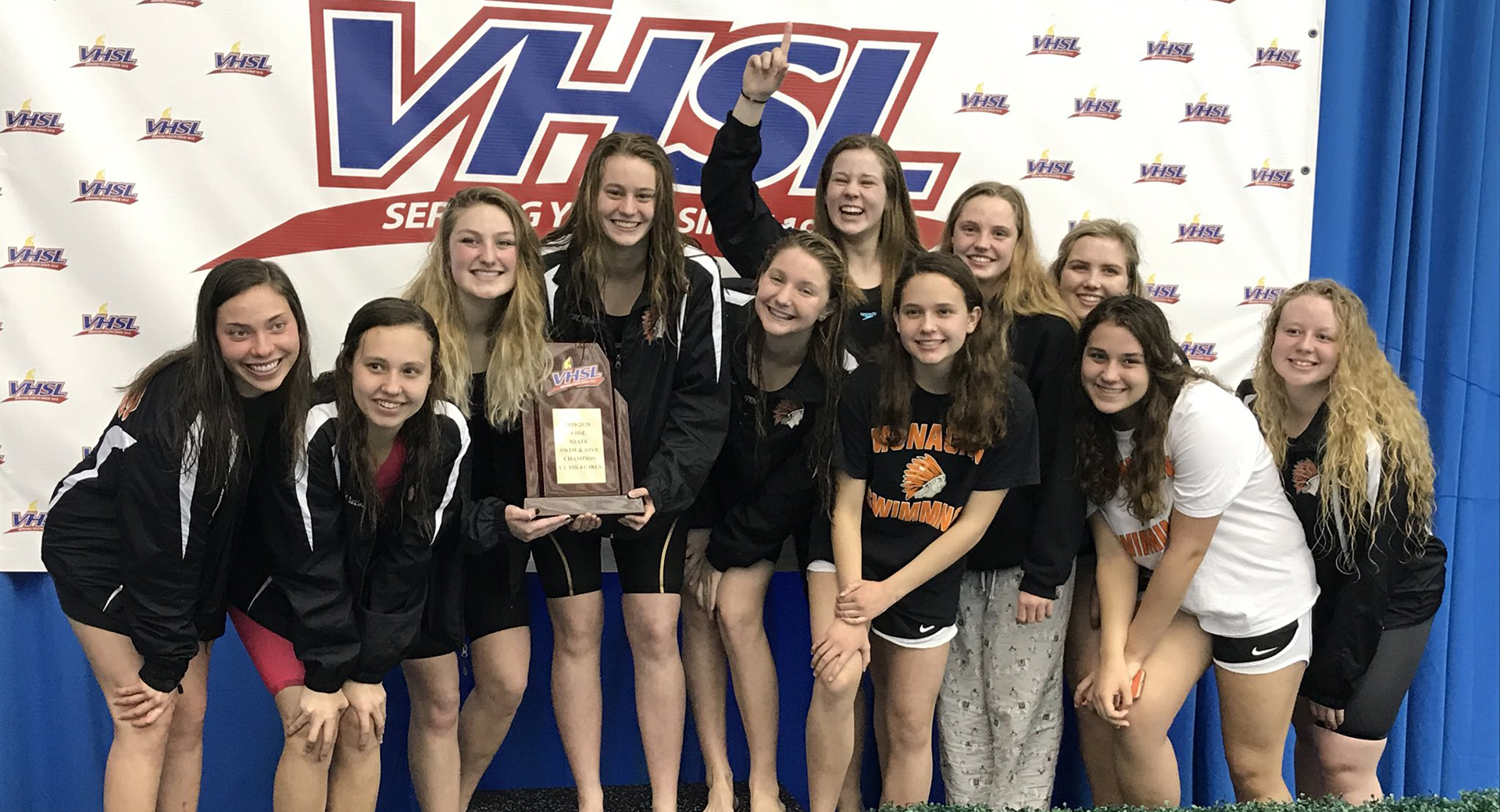 Swimteam on stand accepting award.