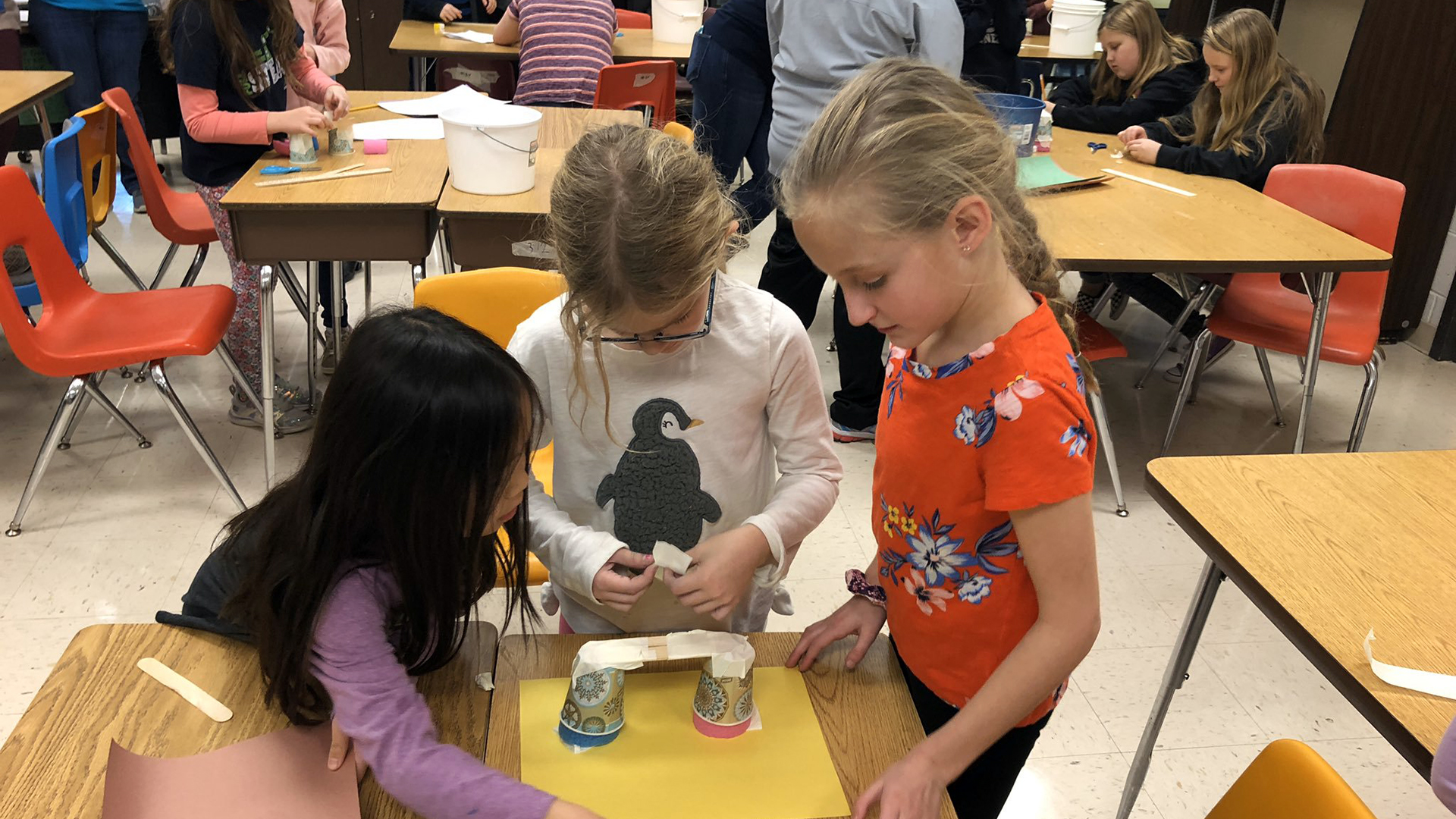 three girls working on a project together in the classroom