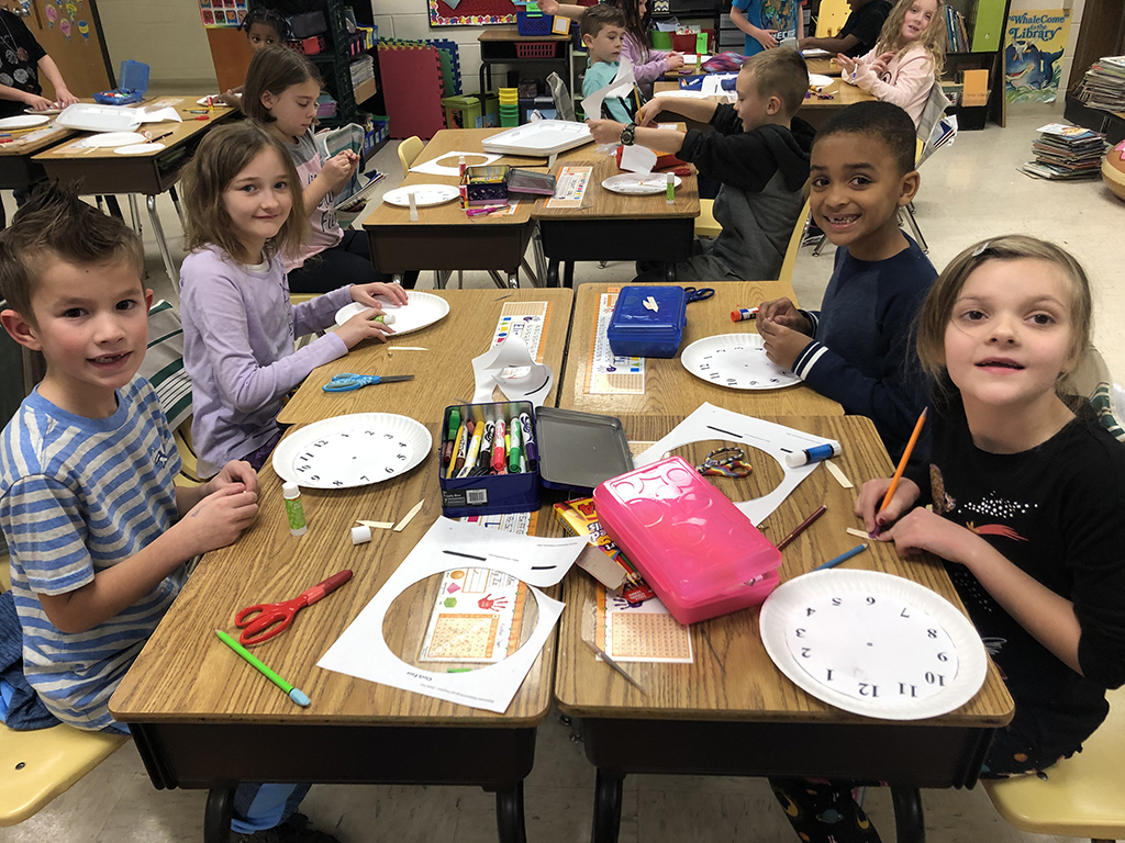 Photo of students at their desks in the classroom working on making a clock with paper plates.