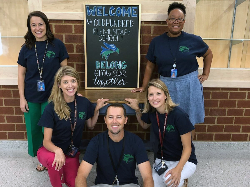 five teachers posing around a sign saying soaring together