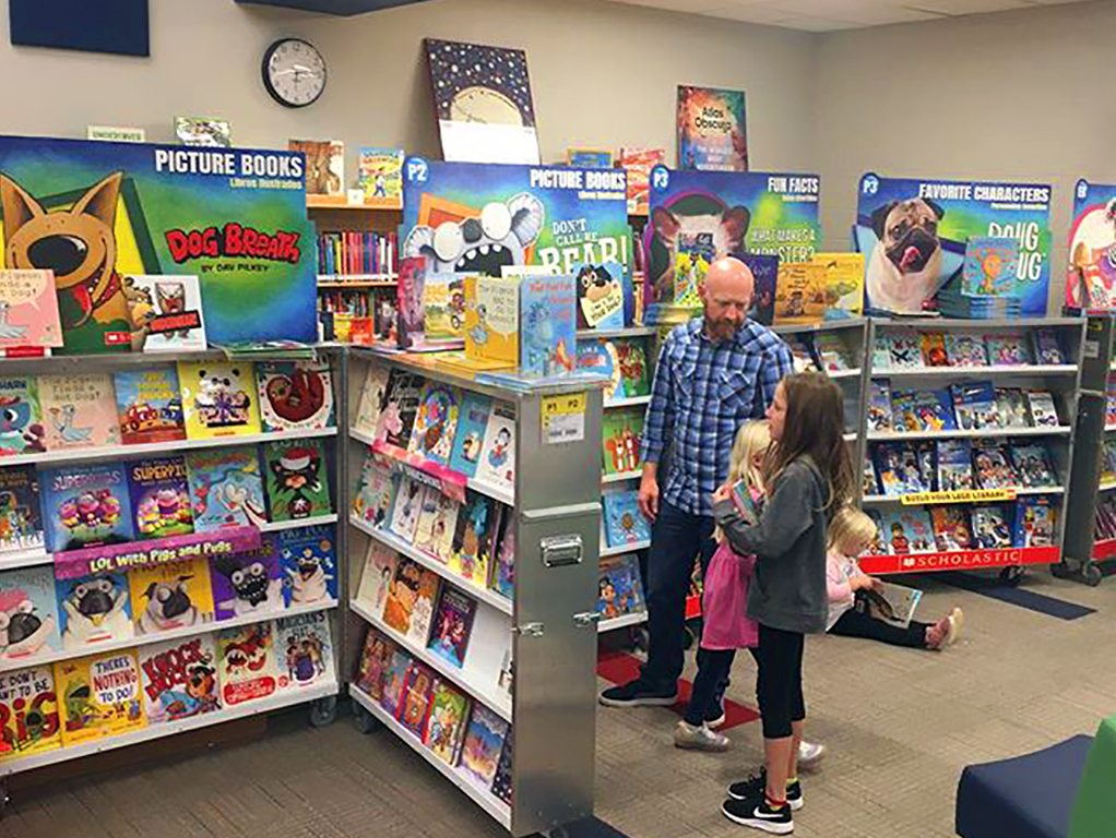 student and teacher look at books in library