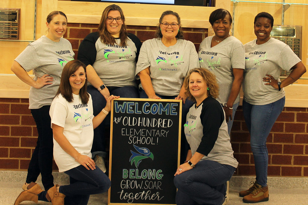 group of six teachers pose in front of sign with motto