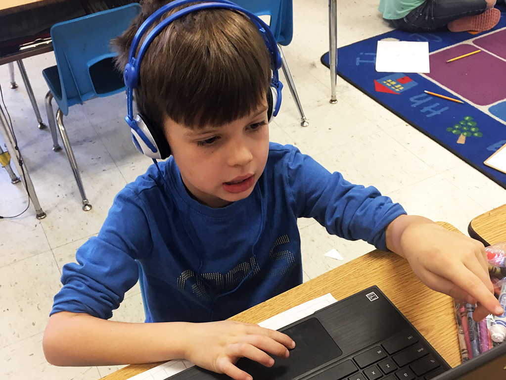 Male student working on computer, wearing headphones.