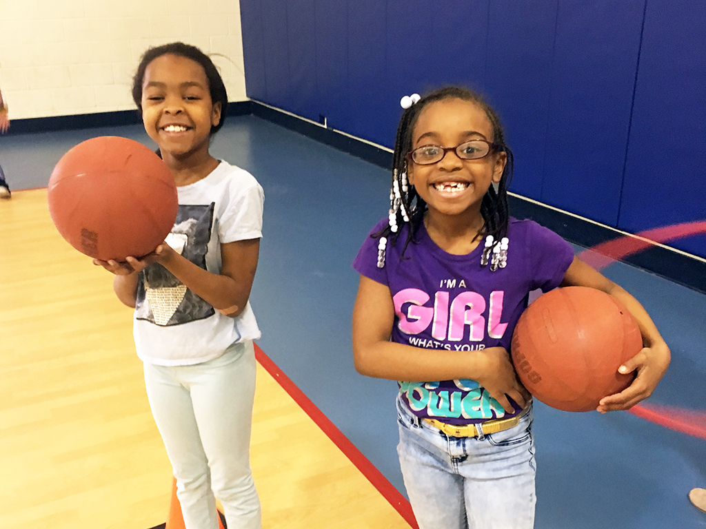 Two girls holding basketballs in the gym and smiling for the camera.