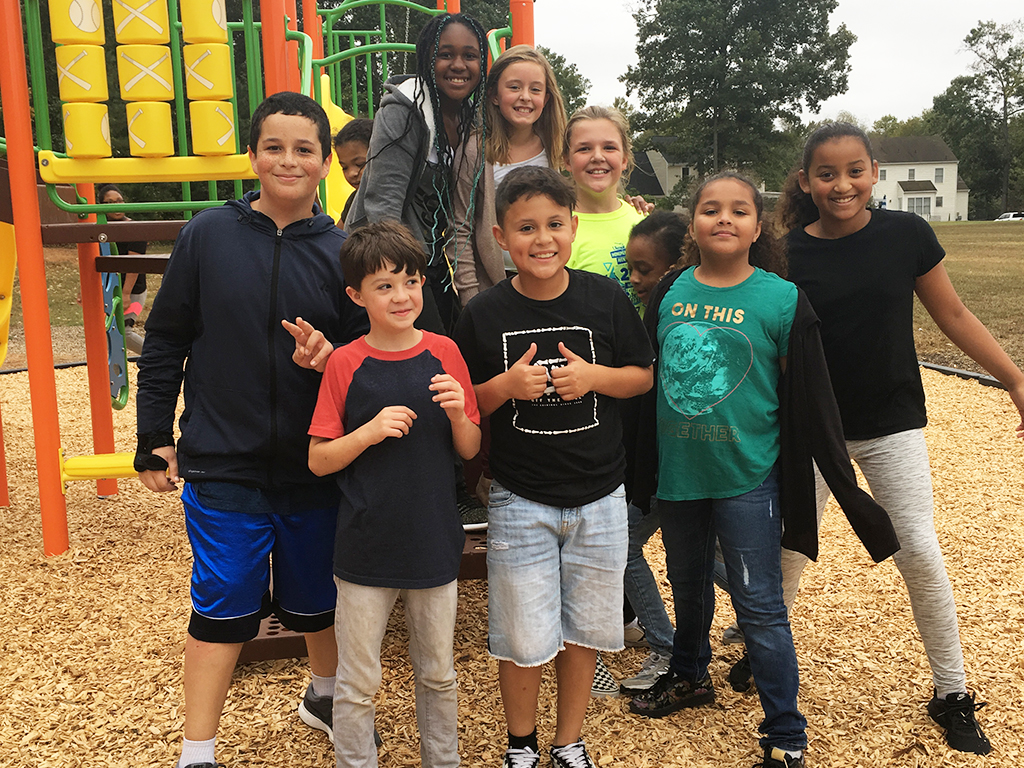 Group of students on playground pose for a group photo.