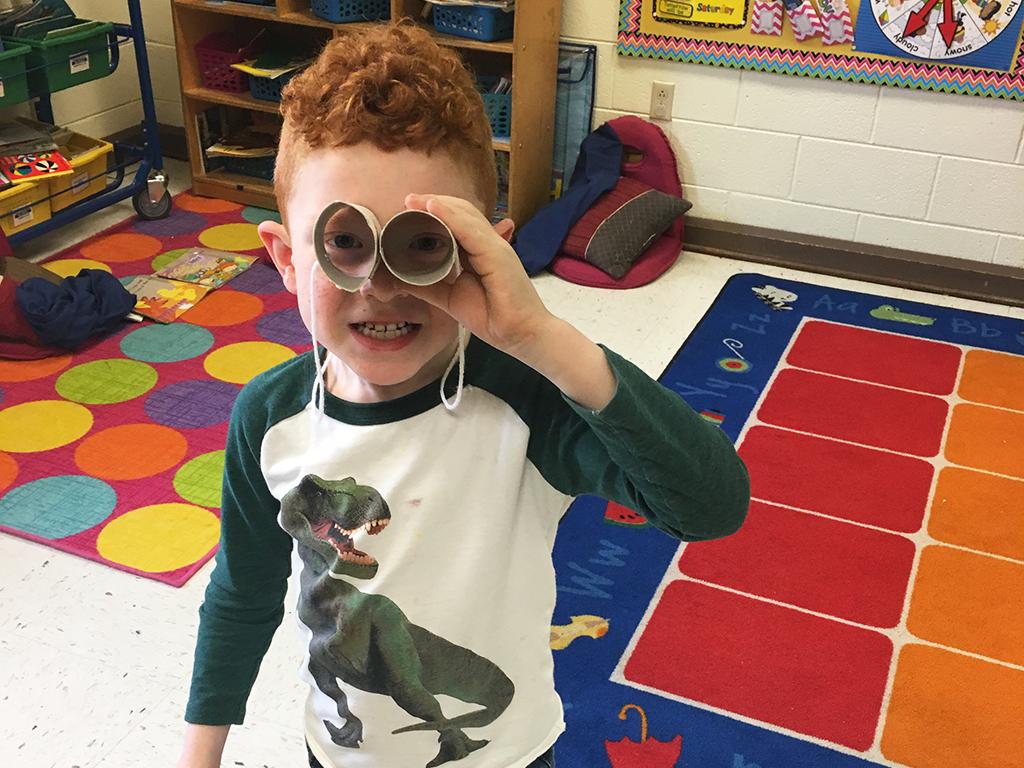 Boy looking through binoculars he made from toilet paper rolls.