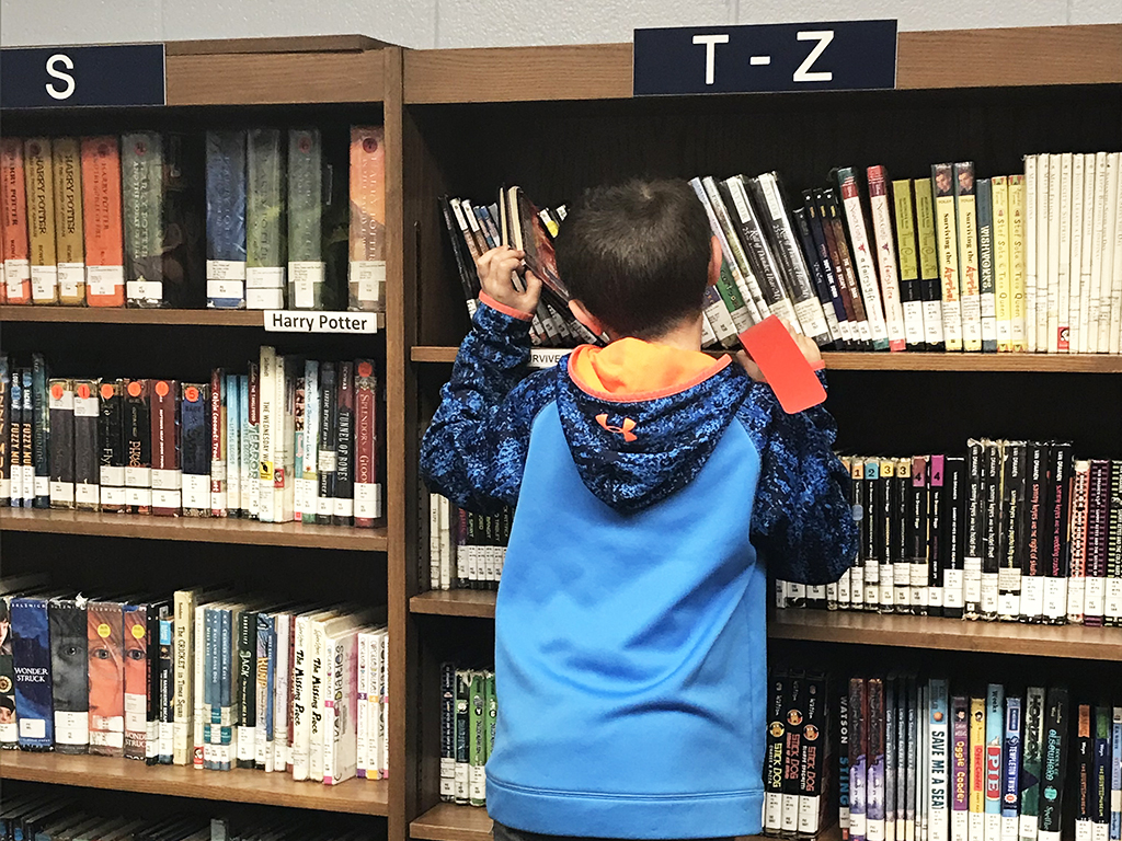 Student standing on a stool in front of book shelves searching for a book.
