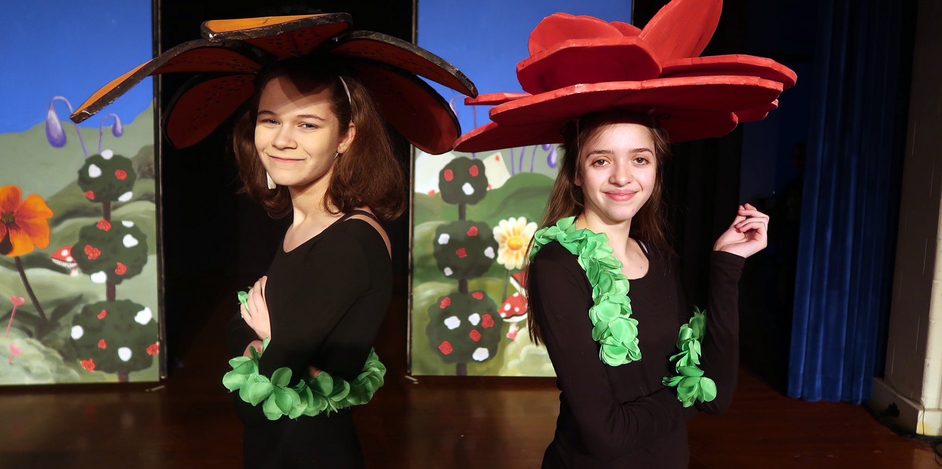 Two female students dressing in costume and silly hats for school play.