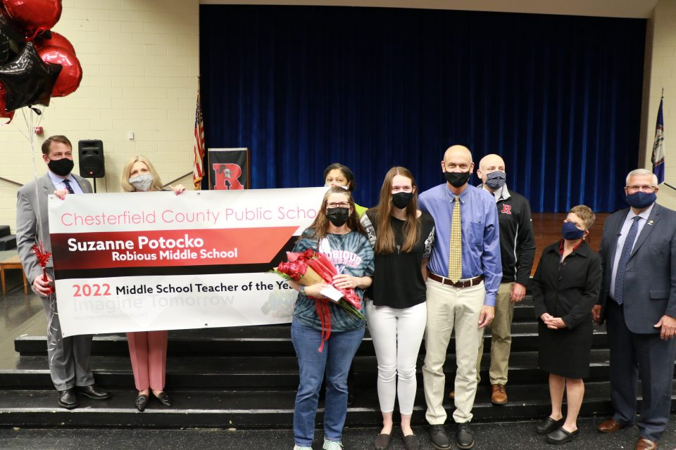 Teacher posing with family and school leadership holding a giant congratulations banner.
